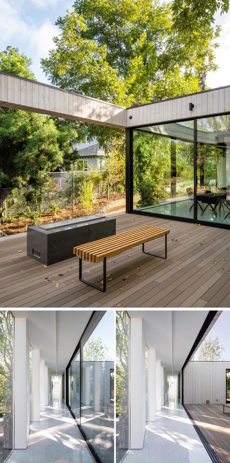 The glass walls in the dining room and hallway of this modern house slide open to give access to a deck that's home to an outdoor fire. #GlassWalls #Deck #Hallway #Windows