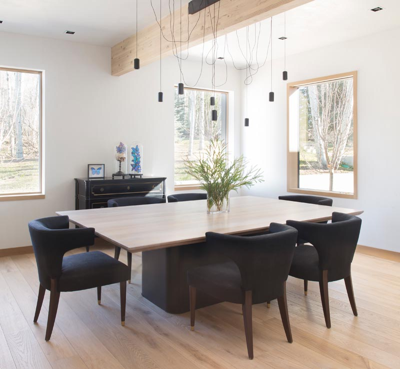 This modern dining room has contrasting elements, like a black table base and wood table top, black chairs furnishings and white walls. #DiningRoom #ModernDiningRoom