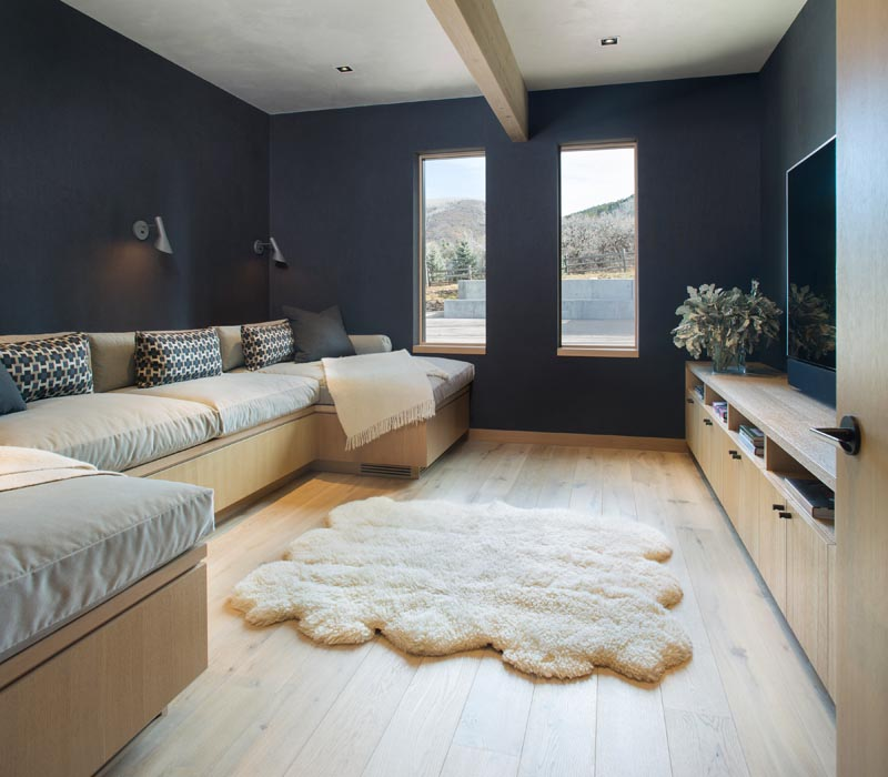 In this modern family room, there's a large couch and dark walls, creating the ideal environment for movie night. #FamilyRoom #InteriorDesign #ModernMovieRoom