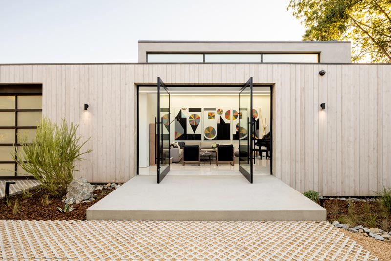Welcoming visitors to this modern house are a pair of pivoting glass front doors that lead straight into the living room. #FrontDoor #GlassFrontDoor #PivotingDoor