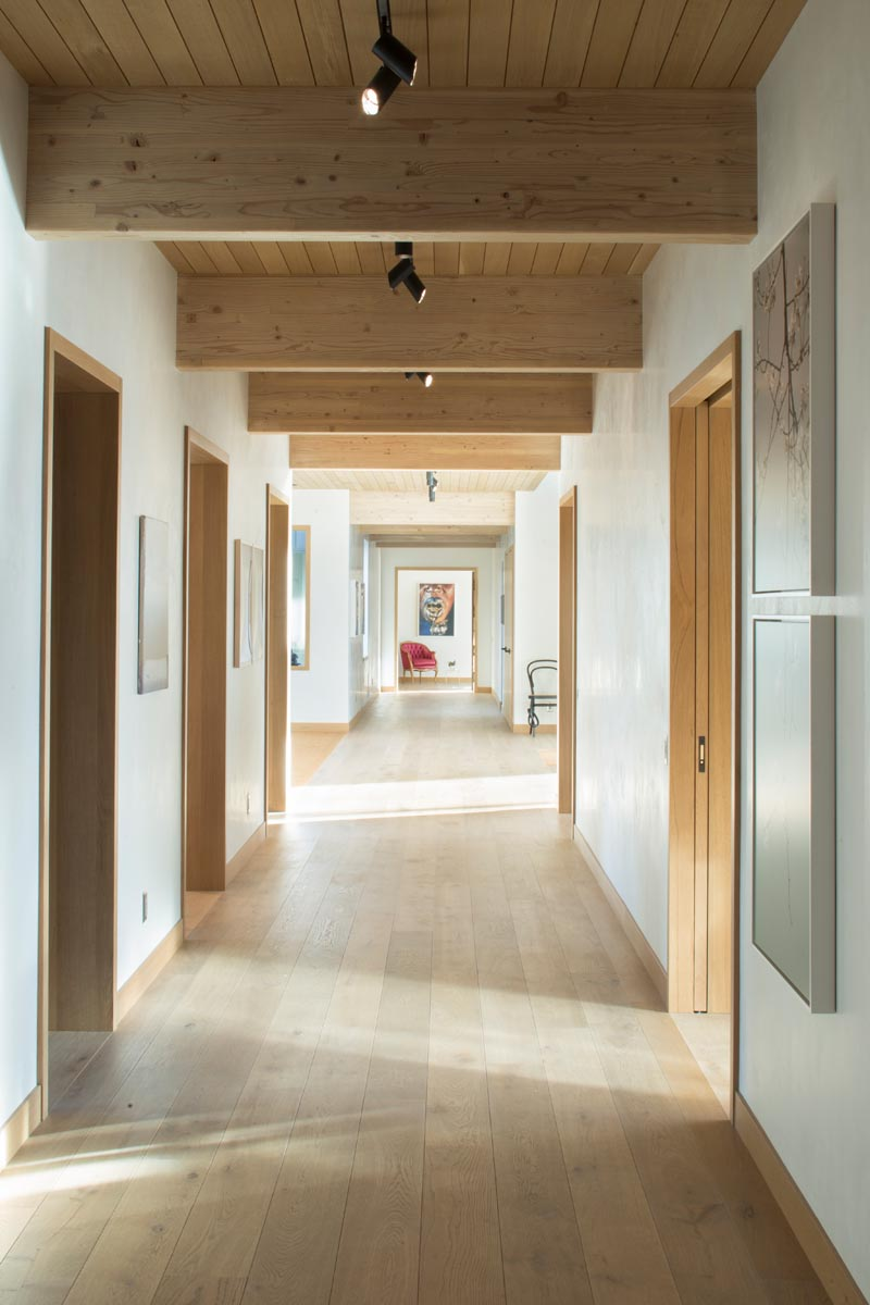 A hallway running the length of this house has wood framed doors that provide access to the various other areas of the house. #ModernHallway #WoodFloors