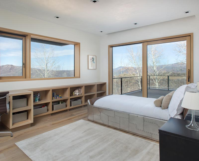 In this modern children's bedroom, a row of shelving lines the wall and merges with a desk, while a sliding glass door opens to a balcony.  #ChildrensBedroom #KidsBedroom #Shelving