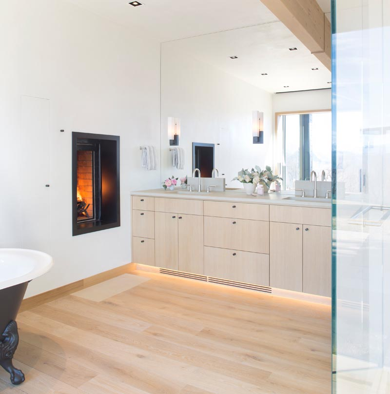 In this modern en-suite master bathroom, a wood vanity sits below a full wall mirror that reflects the light from the window, while the fireplace adds warmth and a sense of relaxation to the space. #MasterBathroom #BathroomDesign #WoodVanity #Fireplace