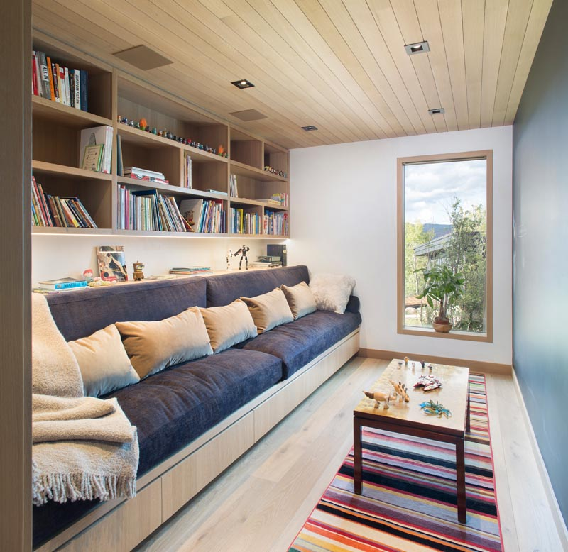 This modern room's dedicated to reading and playing, with a comfortable couch and shelving that runs the length of the room. #ModernReadingRoom #ModernPlayRoom #ModernHomeLibrary