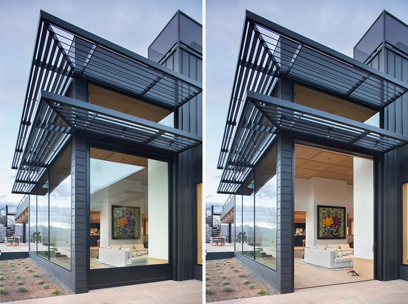 A large black-framed glass pocket door opens connects the living room with the exterior of this modern house. #Doors #PocketDoor