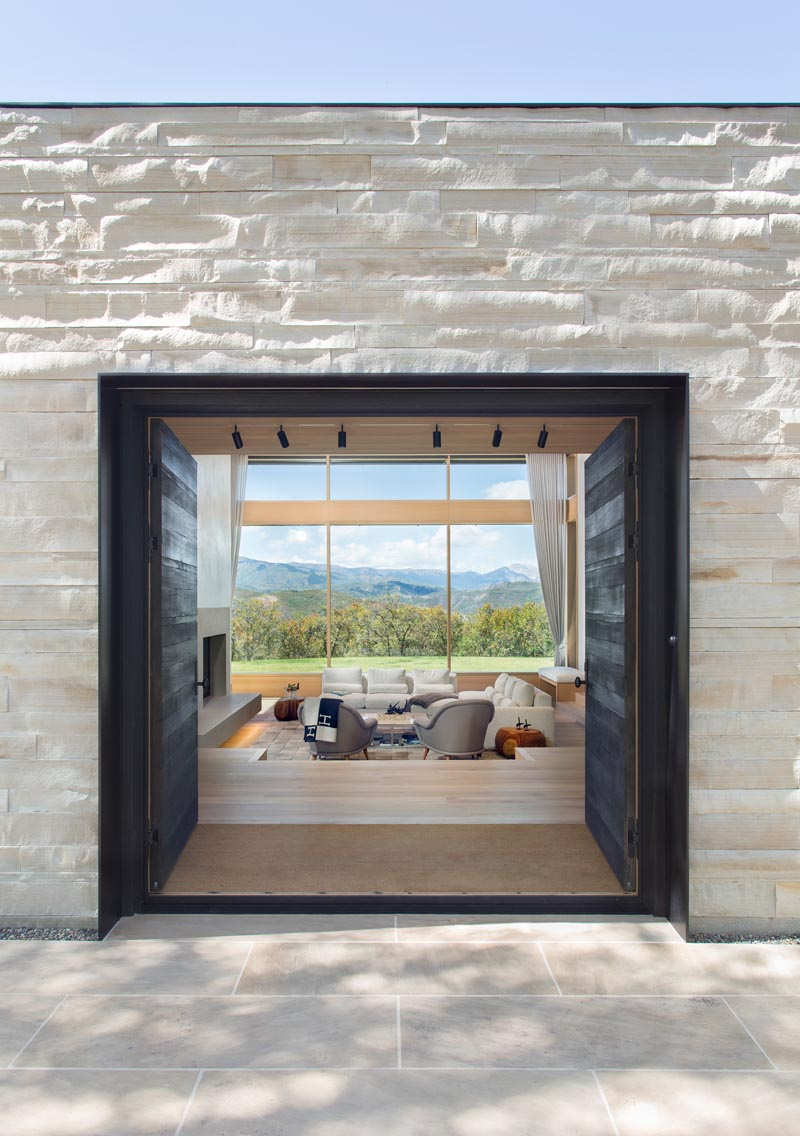 This large front door creates a dramatic entrance and contrasts the exterior staggered, remnant stone walls that are aligned with interior walls that run in a single direction, allowing light and landscape to slip past. #ModernFrontDoors #StoneWallExterior #StoneFacade