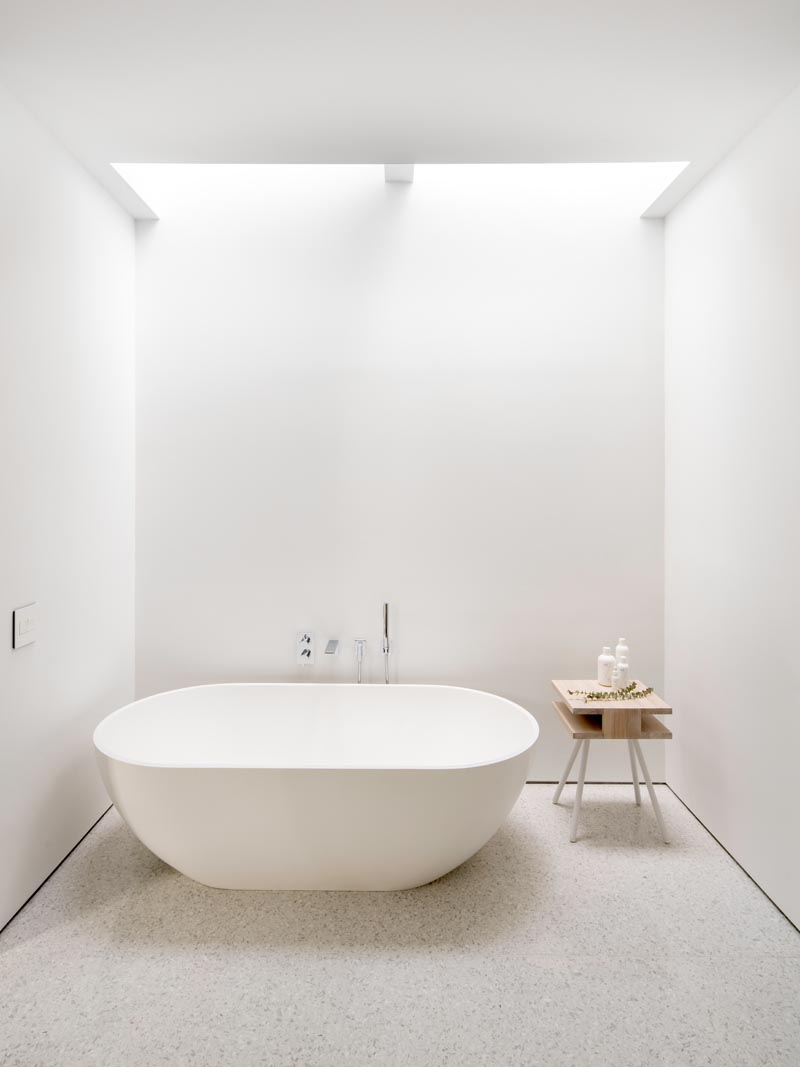 In this modern master bathroom, the freestanding bathtub is located directly below skylights, allowing the user to look up to the sky as they relax. #Bathroom #MasterBathroom #WhiteBathroom