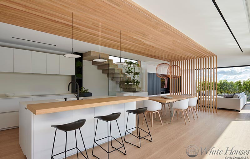 This Combined Kitchen And Dining Room Is Defined By An Overhead Wood Accent