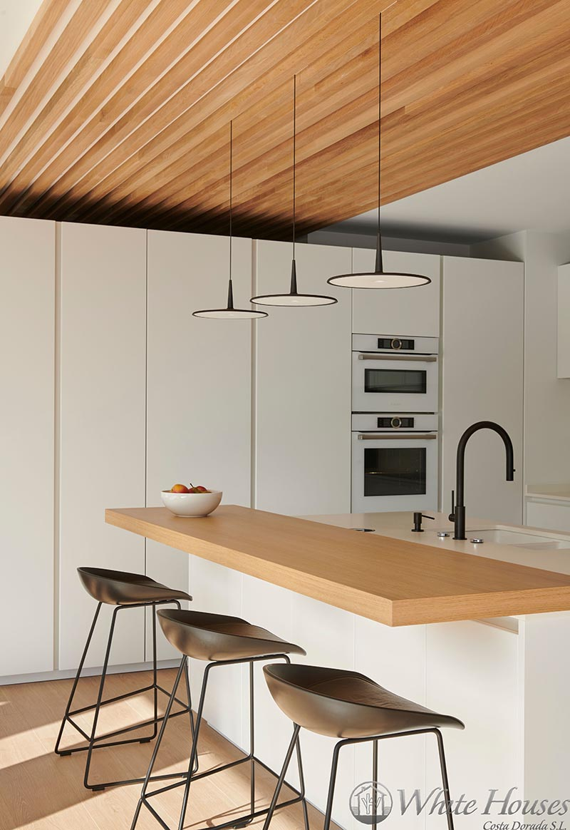 In this modern kitchen, white appliances have been chosen to blend in with the surrounding minimalist white cabinets, helping to create a somewhat seamless appearance. #WhiteKitchen #ModernKitchen #KitchenDesign