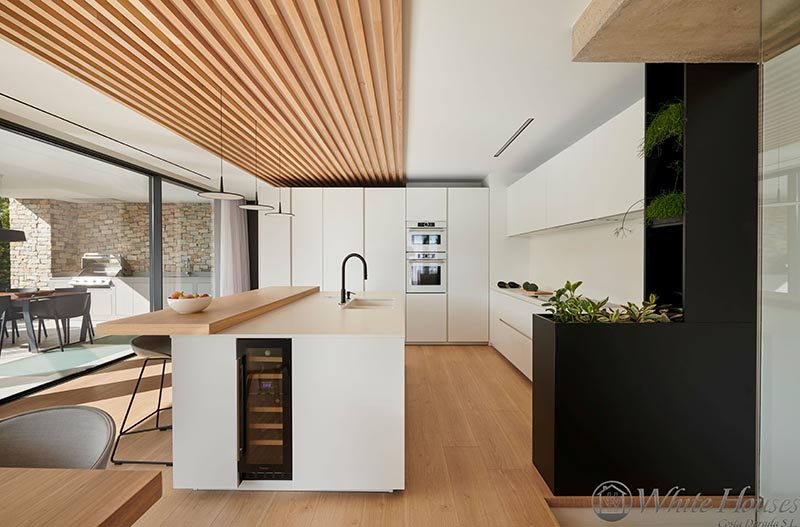 In this modern kitchen, the island has a small built-in wine fridge, while black planter at the end of the cabinets, travels up to the ceiling with shelves for even more plants, adding a contrasting element and a natural touch. #Kitchen #ModernKitchen #WineFrige #Planter