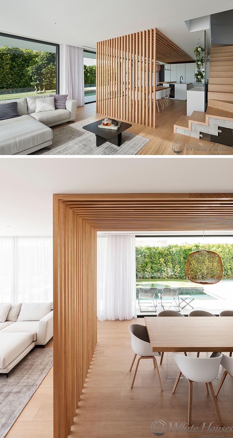 Connecting and defining this modern kitchen and dining area is a wood slat accent that travels from one wall at the end of the kitchen onto the ceiling and through to the dining area, where it becomes a partition wall, separating it from the living room. #KitchenDesign #DiningArea #WoodSlatWall #Partition #ModernKitchen