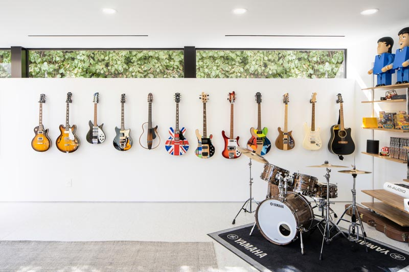 This modern house has a music room furnished with a drum kit and a wall of guitars. #MusicRoom #ModernInterior