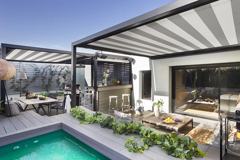 This modern terrace has shade cloths with a striped pattern that add another design element to the space, complementing the black and grey accents used throughout the outdoor space. #ShadeClothes #Terrace #Outdoor Entertaining #SwimmingPool