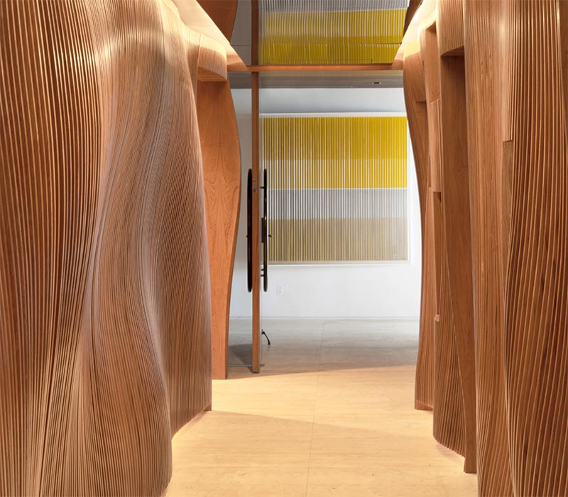 Fernanda Marques Arquitetos Associados has designed an apartment in Miami, Florida, and as part of the design, they included an eye-catching sculptural wood hallway with a mirrored ceiling. #WoodHallway #SculpturalHallway #WavyWoodWall #InteriorDesign #MirroredCeiling