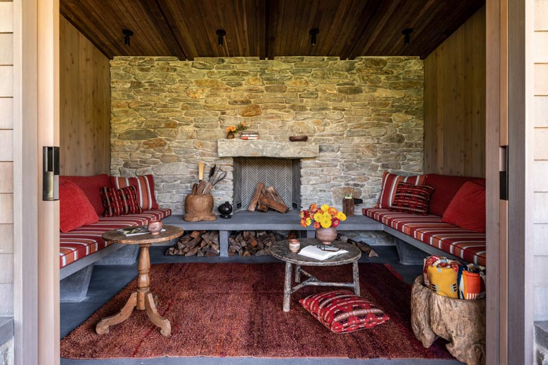 This inglenook, also known as a chimney room, has a cozy feeling with a fireplace surrounded by a stone wall and even further built-in seating.