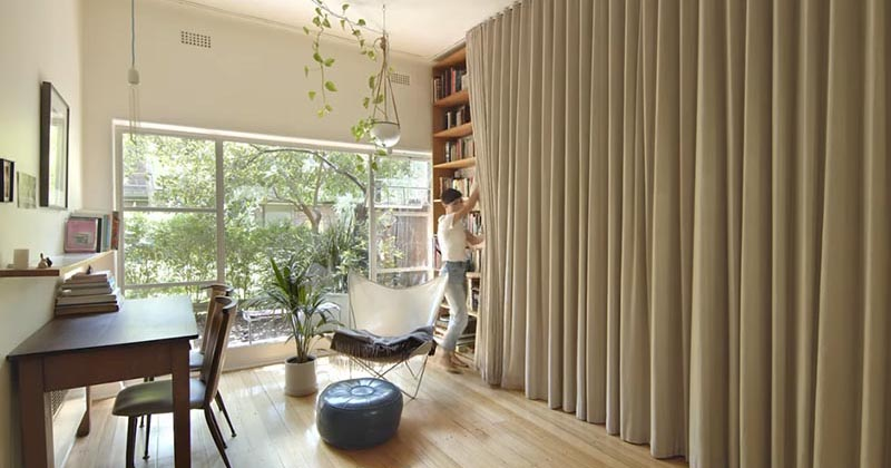 A Floor-To-Ceiling Curtain Hides A Wall Of Storage And Bed In This Small Apartment