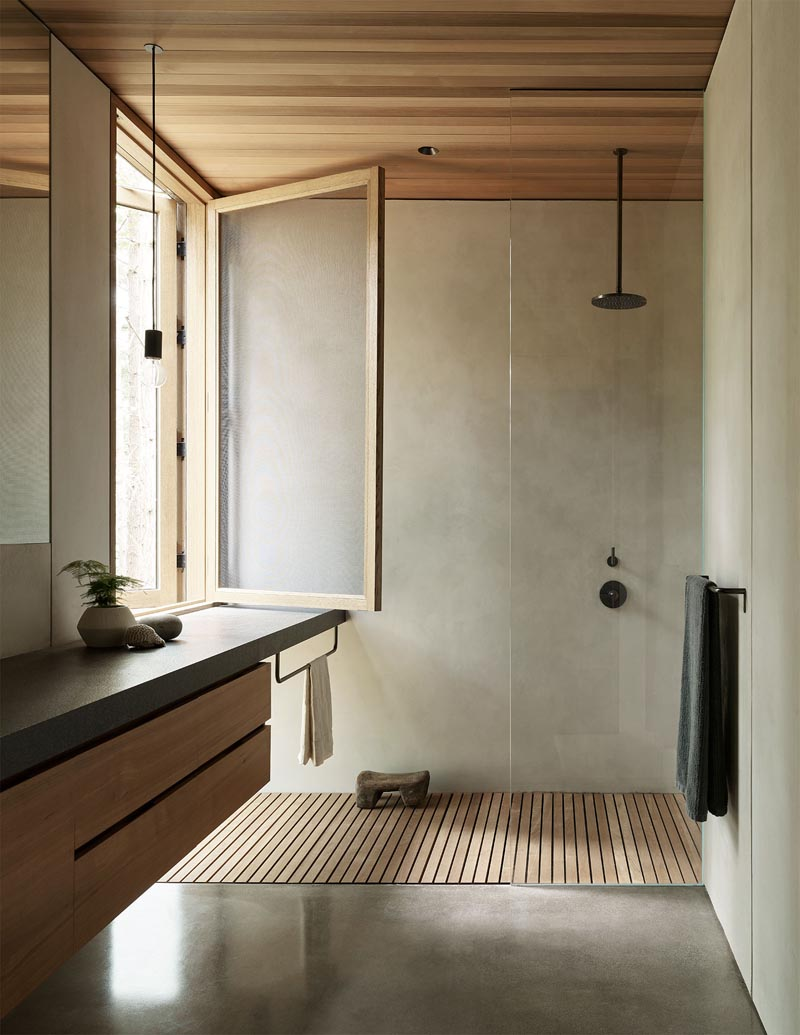In this modern bathroom, there's a large window providing natural light for the shower, while a floating vanity with wood cabinetry complements the wood ceiling. #BathroomDesign #ModernBathroom