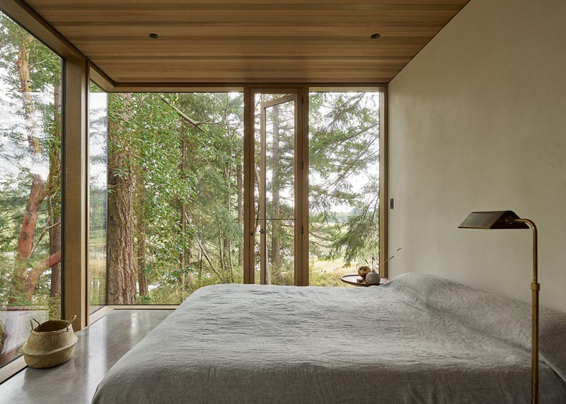 In this minimalist bedroom, the floor-to-ceiling windows provide an uninterrupted view of the surrounding trees. #ModernBedroom #Windows #WoodCeiling