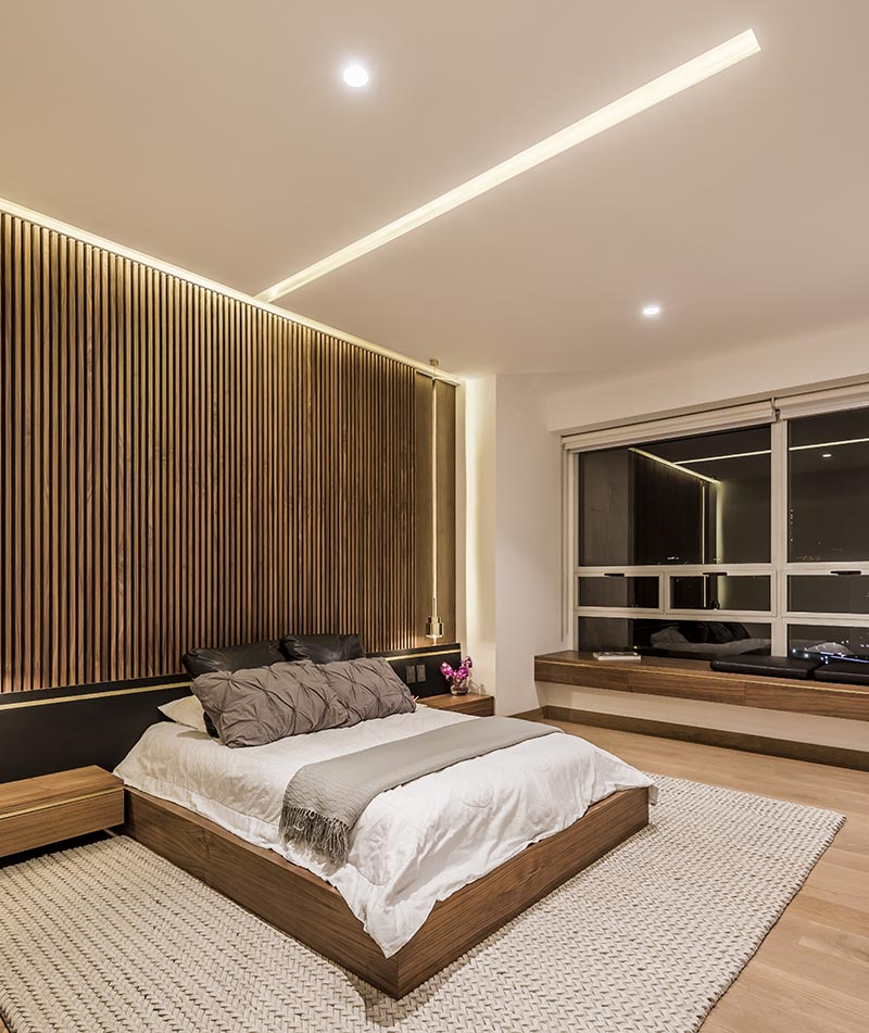 In a modern bedroom, hidden lighting in the ceiling and around the edges of this wood accent wall helps to provides a soft ambient light to the room. #Lighting #BedroomLighting #BedroomIdeas #ModernBedroom