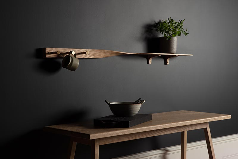 Carefully sculpted from tonal ash wood, the Tor Twist Shelf gently twists in the center and elevates itself above three brushed brass tipped coat pegs. #WoodShelving #WallShelf #ModernShelf #KitchenShelving #EntrywayShelf