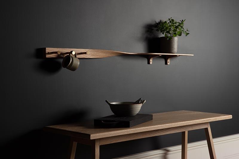 Carefully sculpted from tonal ash wood, the Tor Twist Shelf gently twists in the center and elevates itself above three brushed brass tipped coat pegs. #WoodShelving #WallShelf #ModernShelf #KitchenShelving #EntrywayShelf