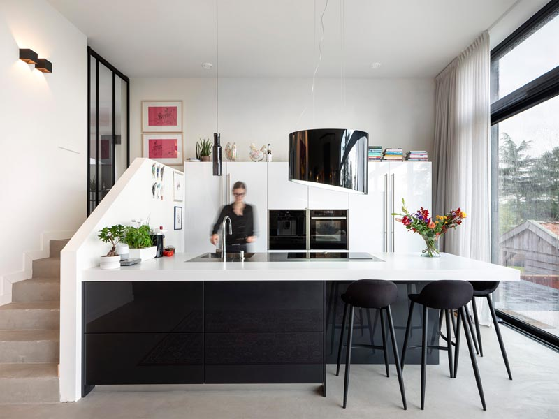 Inside this modern house, steps lead from the front entryway down into the kitchen, that has black accents contrasting the white cabinets and countertop. #ModernKitchen #BlackAndWhite #BlackAndWhiteKitchen #KitchenDesign