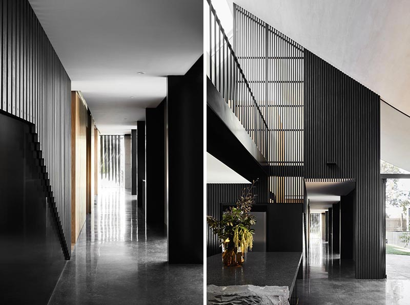 Inside this modern house, there's a long hallway lined with blackened timber slats that leads from the front door, through to the open plan kitchen and dining room. #ModernInterior #Hallway #BlackInterior