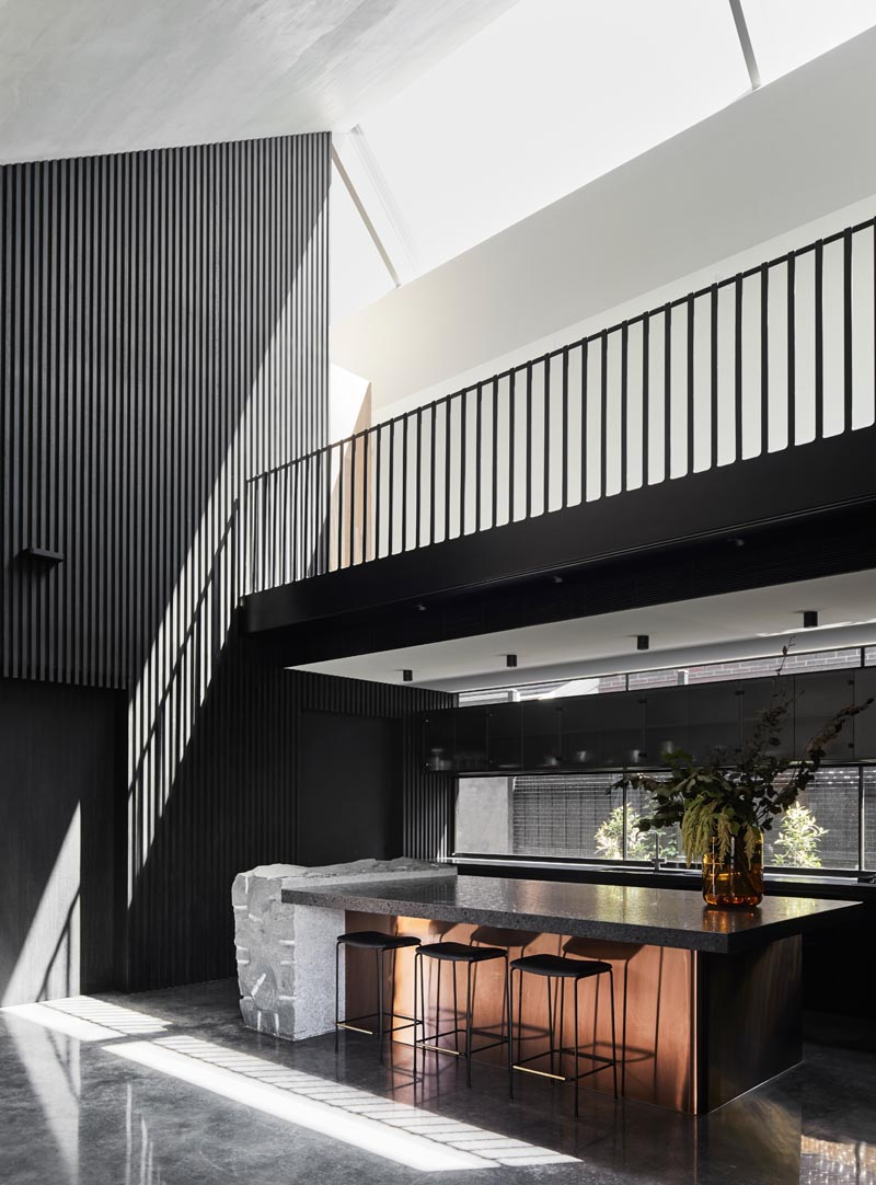 In this modern kitchen, black cabinets are paired with dark countertops, grey stone, and a rose-tone metal accent. #ModernKitchen #BlackKitchen #KitchenIsland