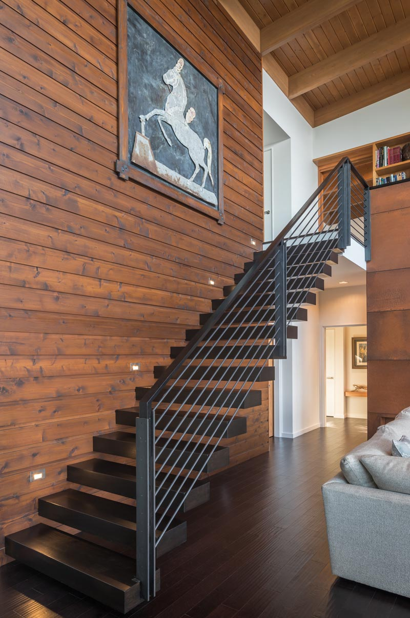 "Cantilevered wood ""floating"" stair treads lead to a library overlooking the double-height living and dining space below. #Stairs #CantileveredStairs #ModernStairs"