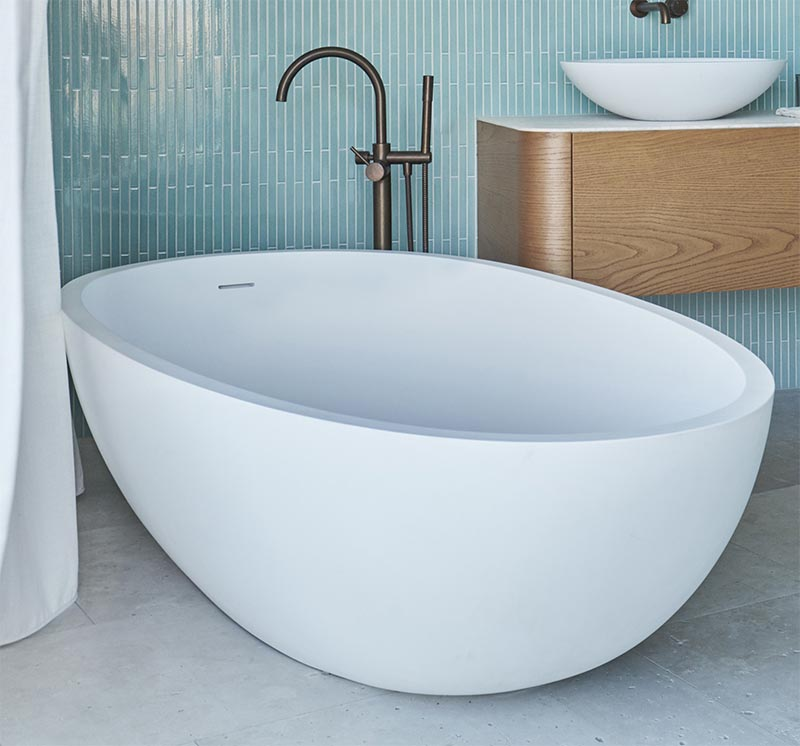 A freestanding white rounded bathtub complements the vanity sinks, while the bronze faucet adds a metallic touch. #ModernBathroom #WhiteBathtub #BathroomDesign