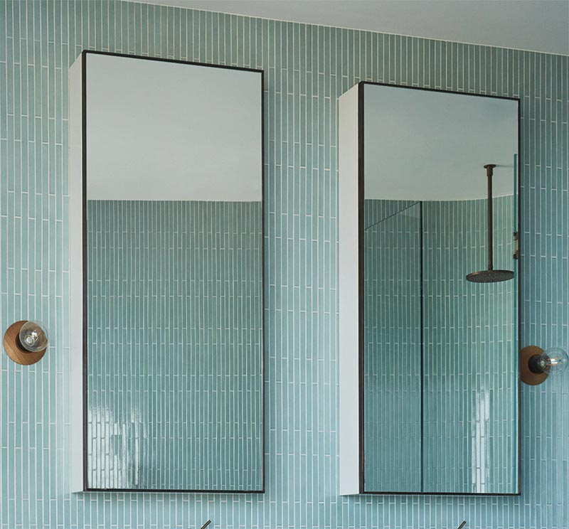 Above the vanity in this modern bathroom is a duo of vertical black framed mirrors. Adjacent to each mirror is a simple sconce with a wood base and an exposed bulb. #BathroomMirrors #ModernBathroom #BlueTIles #BathroomDesign