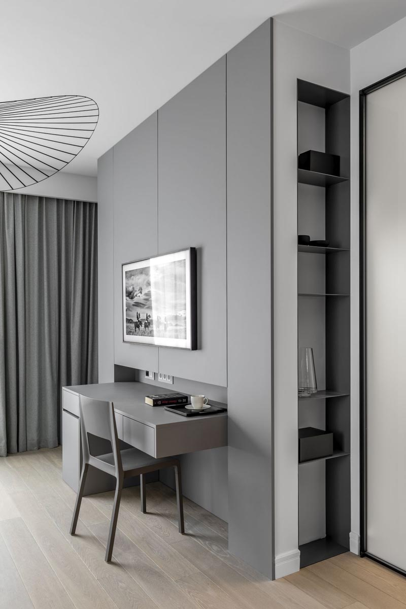 This minimalist grey wall has a built-in desk and shelving niche. #DeskIdeas #ShelvingNiche #GreyWall