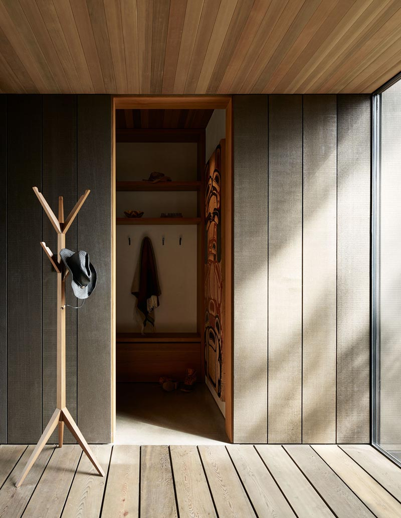Stepping inside this modern house, and, different shapes of wood have been used to create a warm and welcoming atmosphere. Just off the front door is a mud room with a place to hang jackets and store shoes. #ModernEntryway #WoodWalls #WoodCeiling #Mudroom