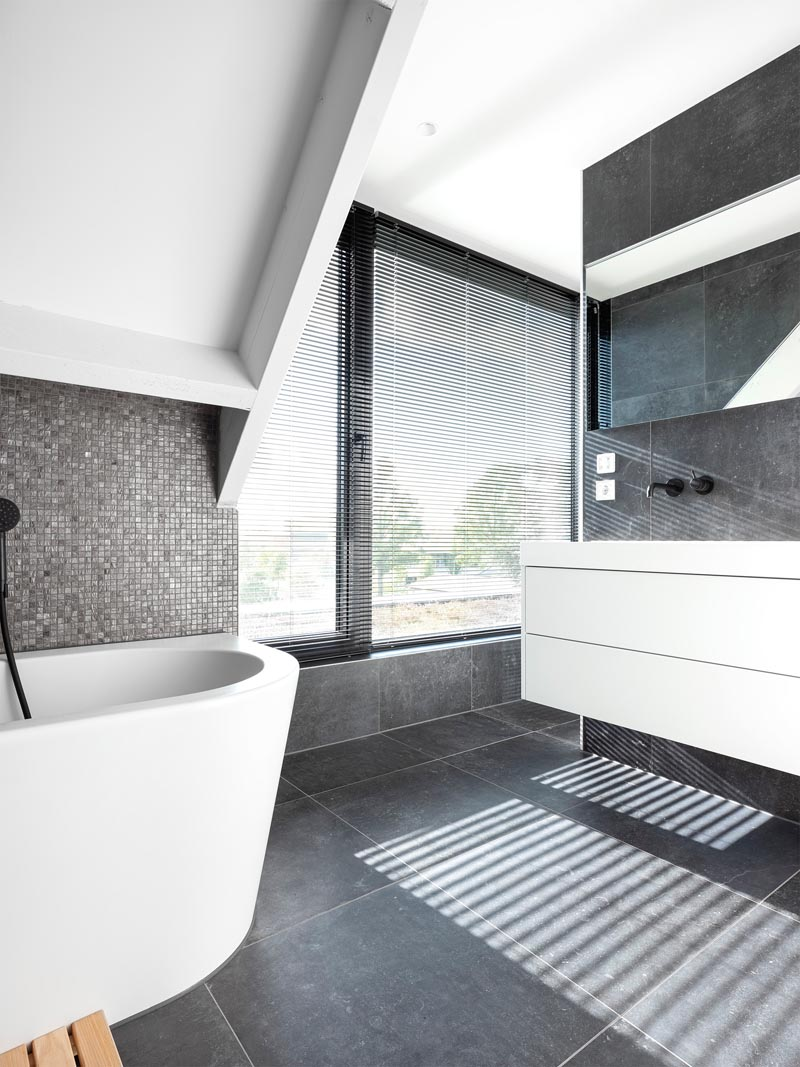 In this modern master bathroom, large format grey tiles cover the floor and walls, while small metallic grey tiles provide a backdrop for the bath. A door opens to a small outdoor space overlooking the back garden. #MasterBathroom #GreyAndWhiteBathroom #BathroomDesign