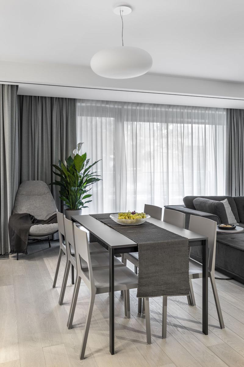 In this modern dining area, a touch of green has been added with a plant, while the floor to ceiling curtains provide privacy and soften the interior. #DiningRoom #GreyCurtains #InteriorDesign
