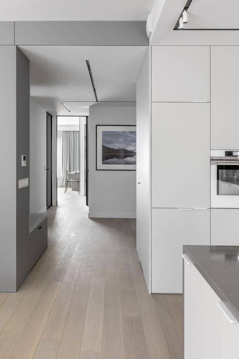 A small hallway connects the social areas of this modern apartment with the bedroom. The hallway also acts as a foyer as it passes by the front door. #ModernApartment #ApartmentDesign #Hallway