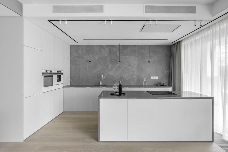 This modern kitchen showcases minimalist white cabinets, grey countertops, and a grey backsplash that covers the wall. #ModernWhiteKitchen #ModernKitchen #GreyCountertops