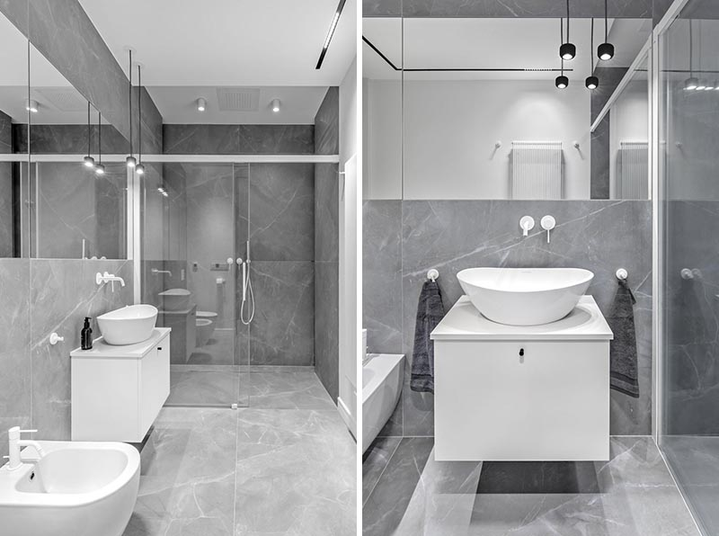 In this modern bathroom, large format grey tiles cover the walls and floors, while a floating white vanity complements the faucets and hardware. #ModernBathroom #BathroomDesign #GreyBathroom