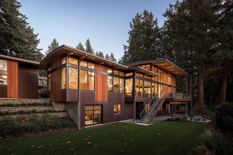 A modern house with plenty of windows, weathering steel, and ipe wood siding.