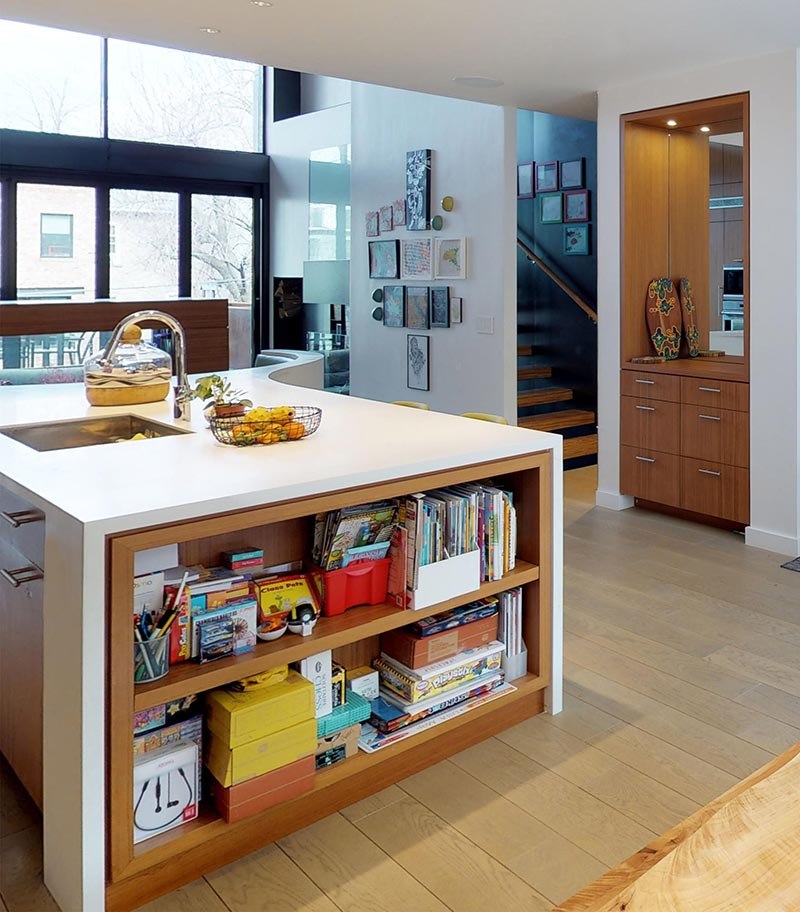 This modern kitchen island features a built-in bookshelf, an undermount sink, and a curved breakfast nook. #KitchenIsland #KitchenDesign #ModernKitchen #KitchenShelving