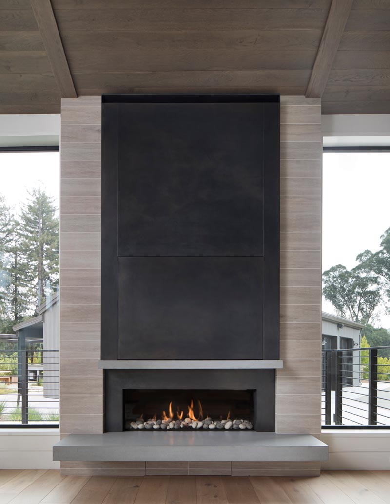 A built-in linear fireplace with a cantilevered hearth and steel surround.