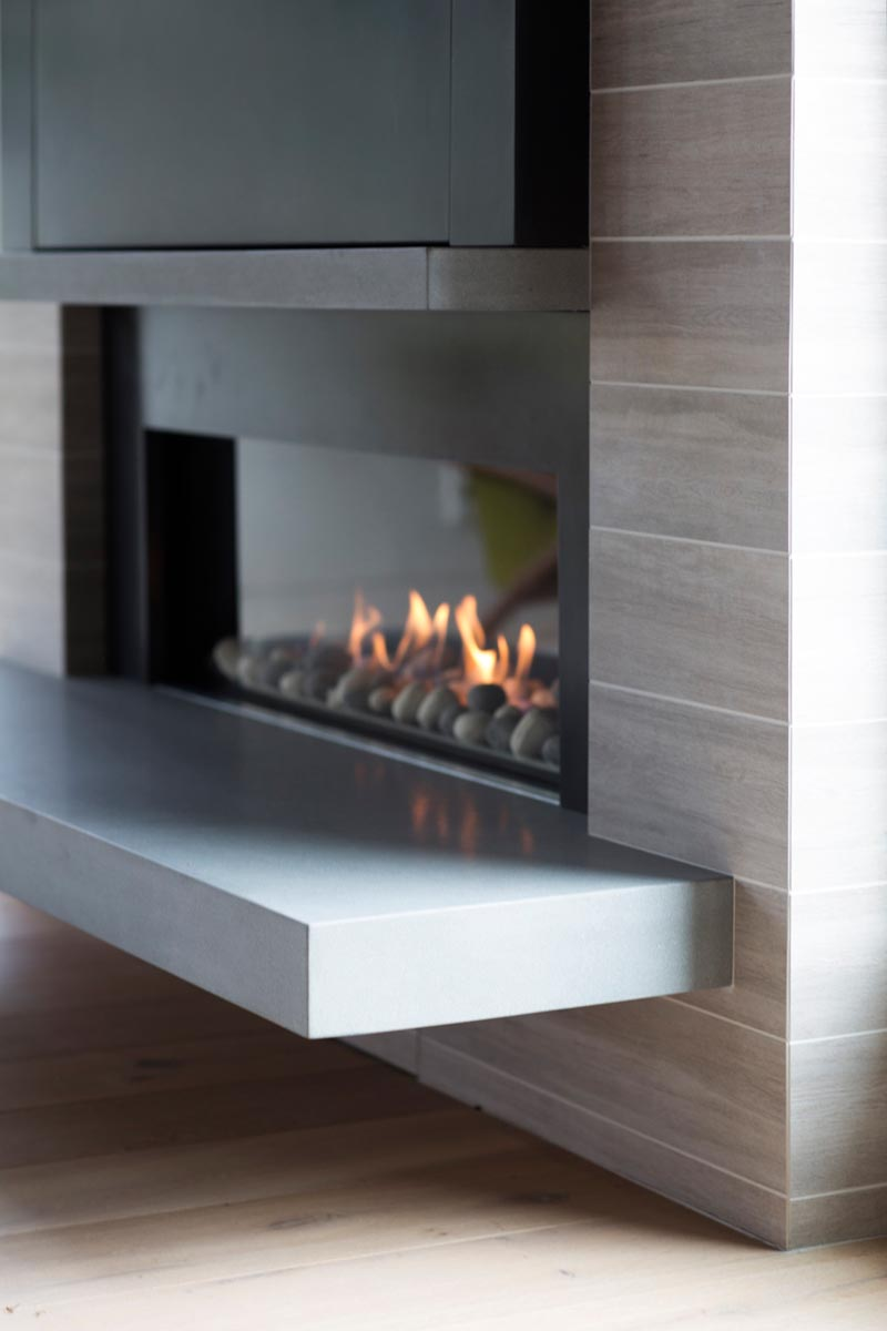 A linear fireplace with a cantilevered hearth and wood-grain tiles.