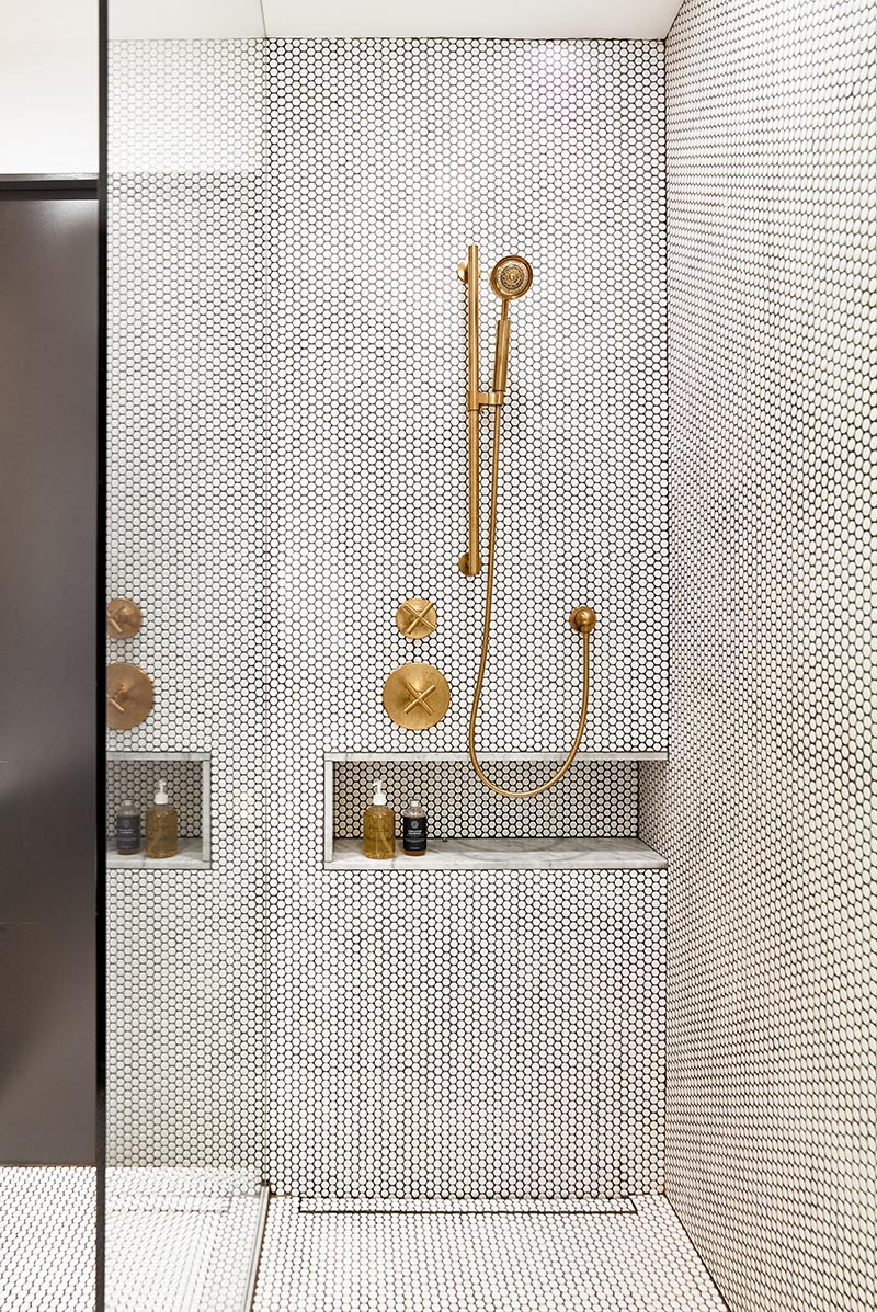 A modern shower with a glass screen, white penny tiles with contrasting black grout, a marble lined shower niche, and brass fixtures. #ModernShower #PennyTile #BrassFixtures #ShowerNiche