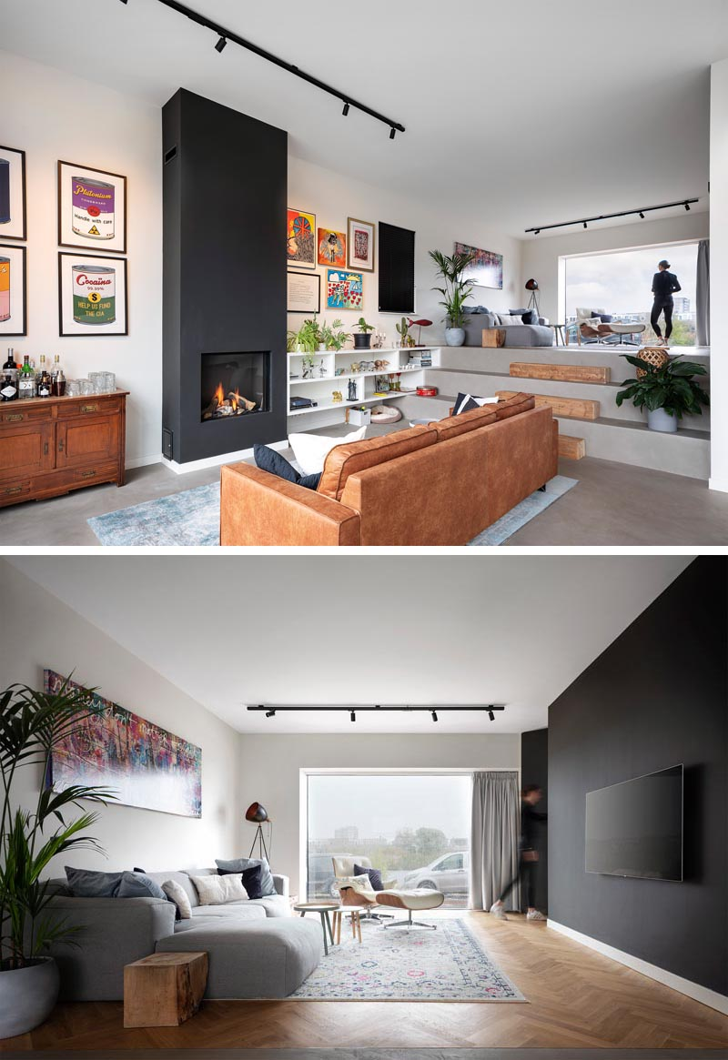 This modern living room that's focused on a fireplace with a black surround, has stairs that double as seating, and lead up to a secondary living space with a large window that looks out to the water. #SplitLevel #LivingRoom #Fireplace