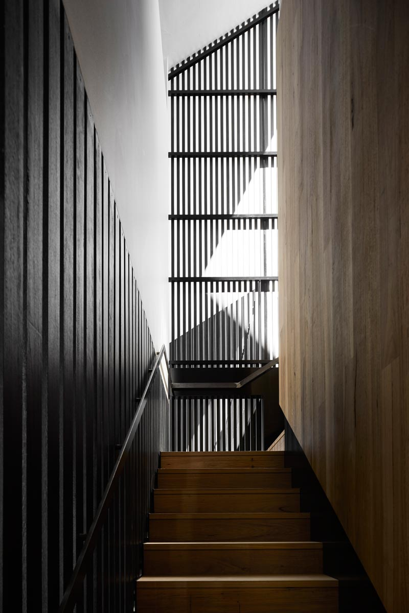 Dark stairs surrounded by blackened wood slats connects the various floors of this modern house. #Stairs #ModernInterior #ModernStairs