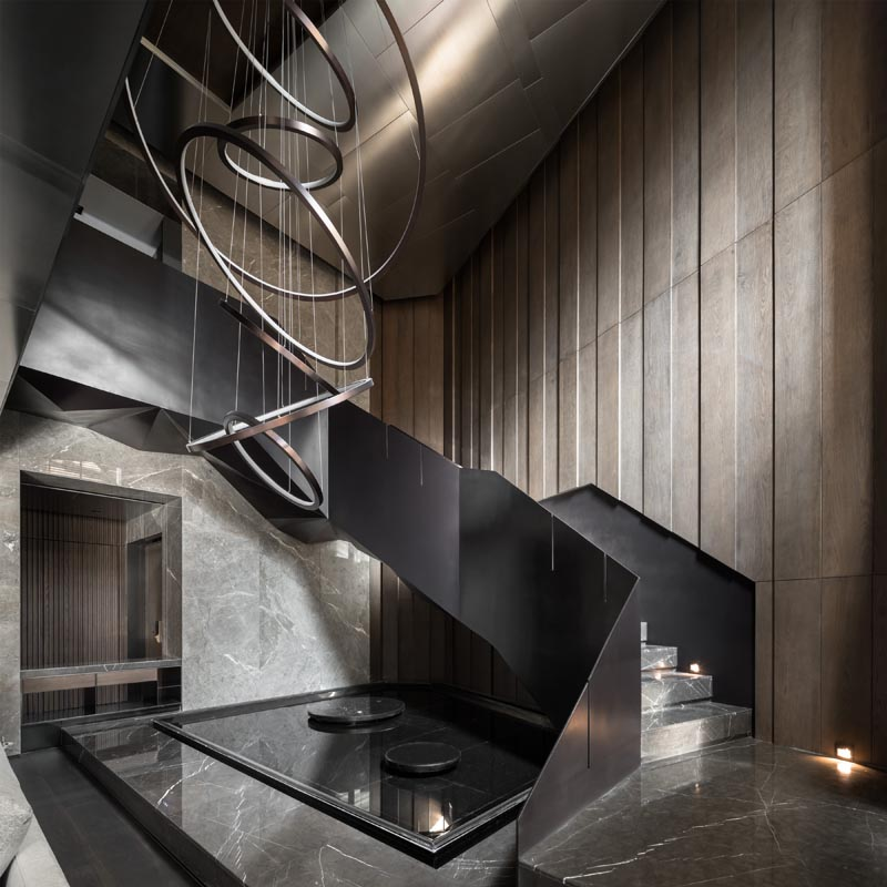 Black steel stairs and a sculptural light add a dramatic flair to this modern interior. #BlackStairs #SteelStairs #Lighting