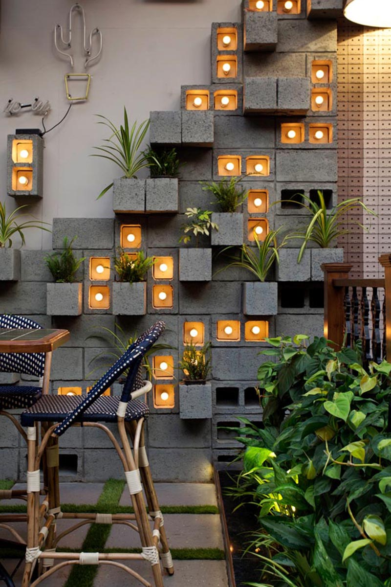 Concrete blocks were used to create this modern eye-catching accent wall, with some of them turned to become planters, slightly protruding to make room for the plants. Other blocks have been turned on their side to make room for individual light bulbs adding a soft glow of the light to the scene. #ConcreteBlockPlantWall #ConcreteBlockPlanter #CinderBlockPlanter