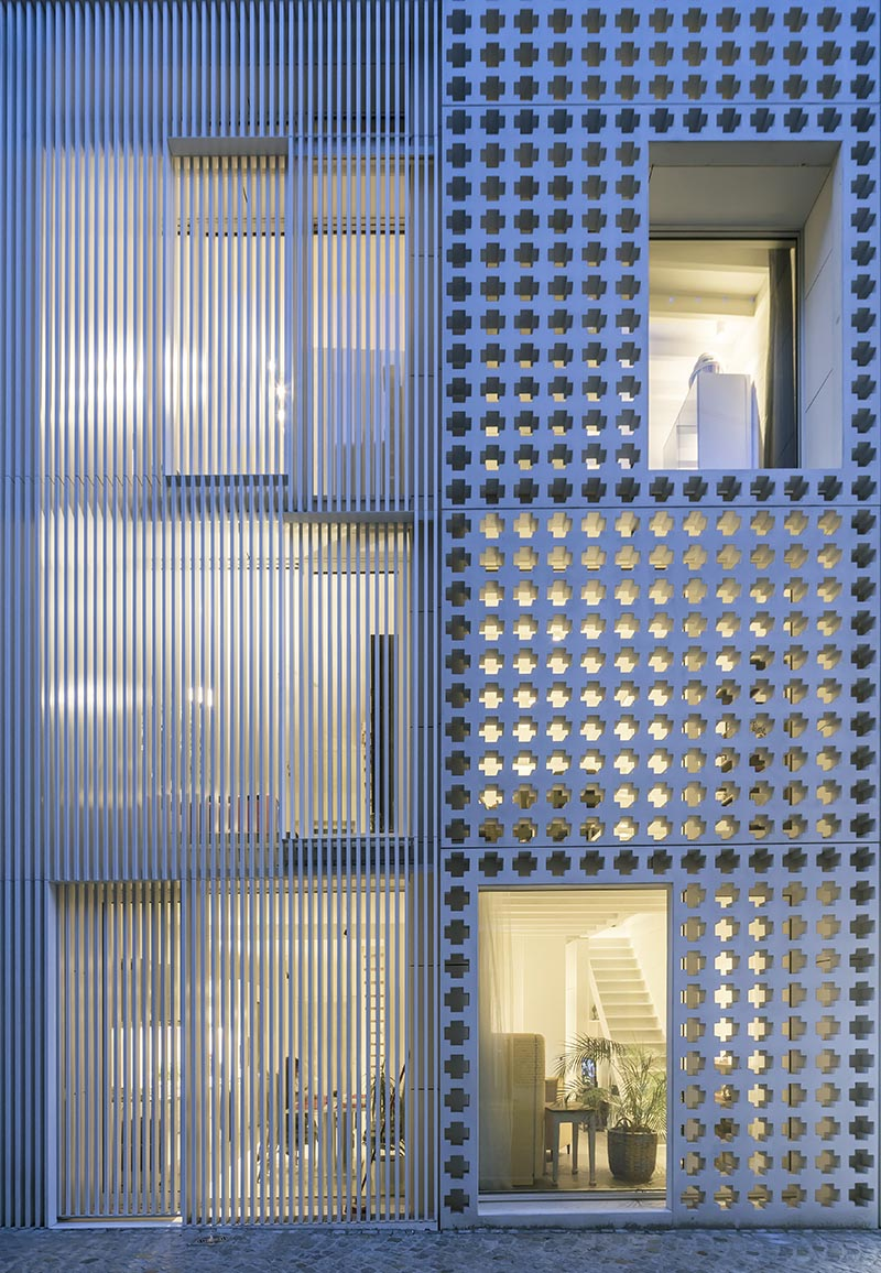 At night, the light from within the apartments highlights the cross-pattern facade and helps to create a shadow effect. #Architecture #PatternedFacade #ModernBuilding