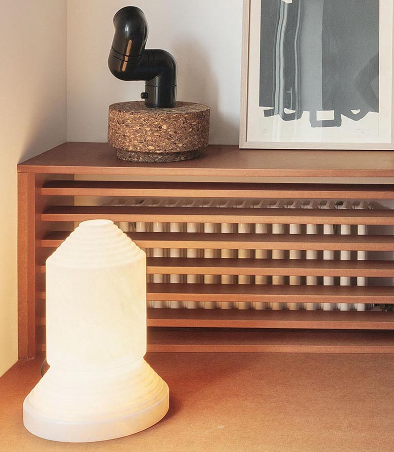 A custom designed shelving unit with a wood slat front is used to hide the radiator in plain sight in the living room of this modern apartment. #HideRadiator #Radiator #LivingRoom