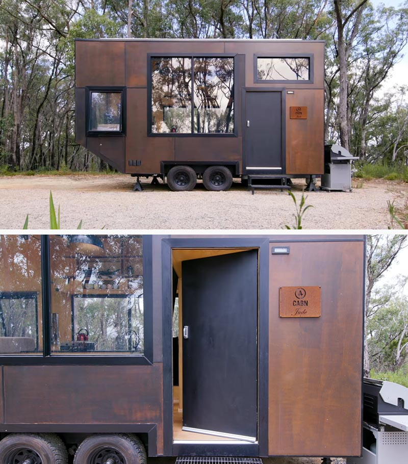 Designed as a getaway for city dwellers to relax in the wilderness, this modern tiny house features an exterior of intentionally mismatched stained panels of marine ply, allowing it to withstand the weather conditions and blend in with the surrounding landscape. #TinyHouse #TinyHome #ModernTinyHouse #BlackWindowFrames